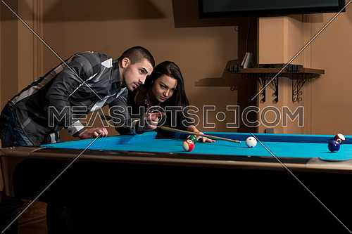 Young Caucasian Woman Receiving Advice On Shooting Pool Ball While Playing Billiards