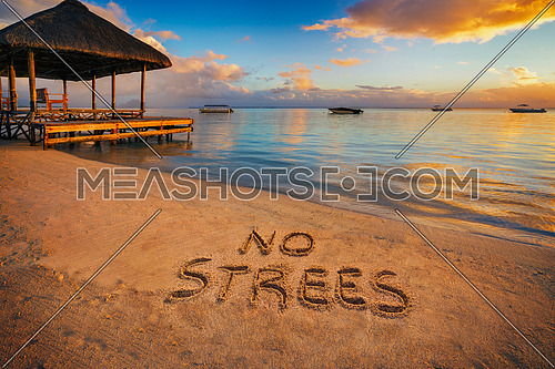 """Forground written in the sand """"No stress"""" at sunset in Mauritius Island with Jetty silhouette and Fishermen's boats in the background."""