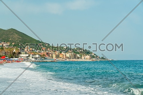 view from the sea of Varazze beach, a village of northern Italy, on the sea, during a beautiful summer day, landscape beach with typical sun parasol and wonderful mediterranean wave.Copy space.