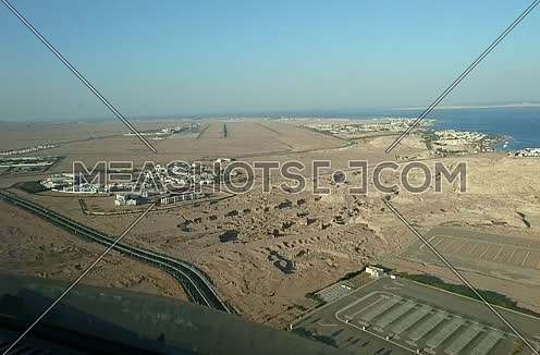 POV shot from plane front while flying towards runway at day