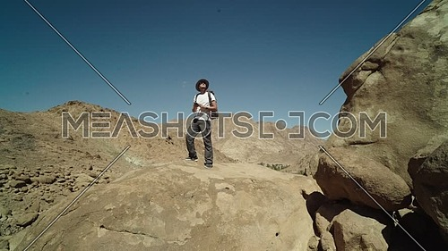 Long shot for a male tourist wearing a pink cap and travel backpack taking photos using mobile phone at Sinai Mountain for wadi Freij at day.