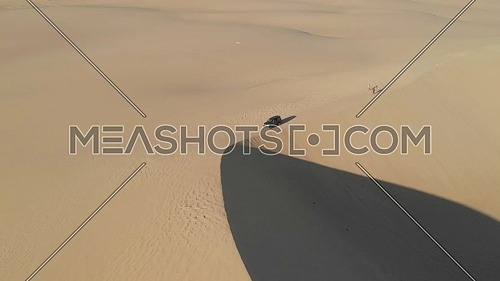 Drone shot of a. 4x4 on the edge of a dune in Siwa, Egypt