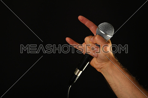 Male hand holding microphone with devil horns rock metal sign isolated on black background