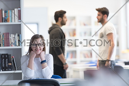 female smart looking student study in school library, group of students in background