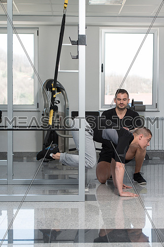 Personal Trainer Showing Young Man How To Train With Trx Fitness Straps In A Health And Fitness Concept