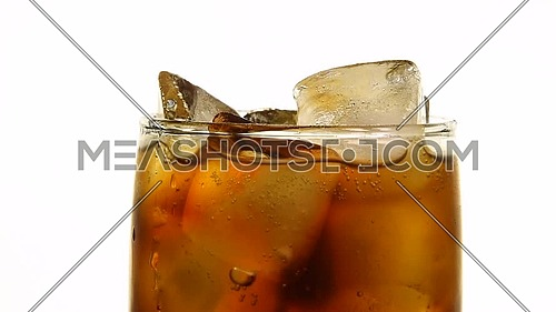 Extreme close up full glass of carbonated cola soft drink with ice cubes over white background, low angle side view, slow motion