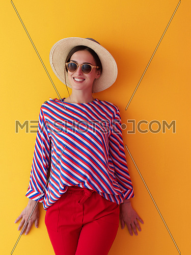 Portrait of young woman wearing sunglasses and hat over a yellow background. Female model posing in the studio. Concept of fashion