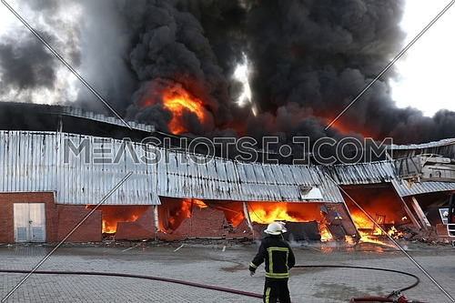 Large fire in a warehouse with huge flames and a fireman