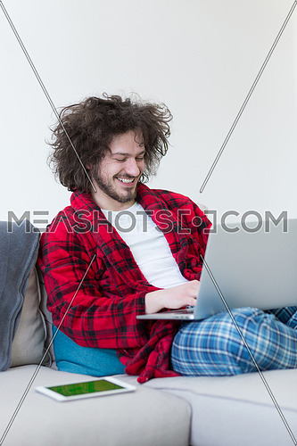 young freelancer in bathrobe working from home using laptop computer while sitting on sofa