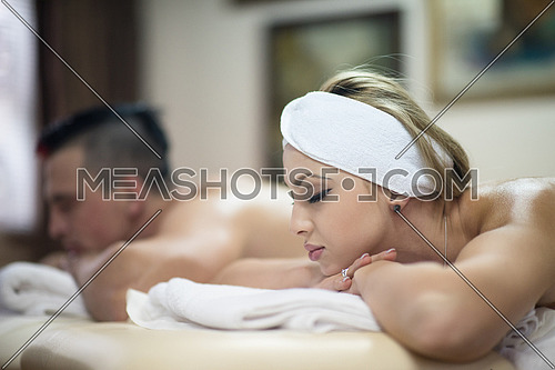 relaxed young couple getting massage in spa and wellness salon
