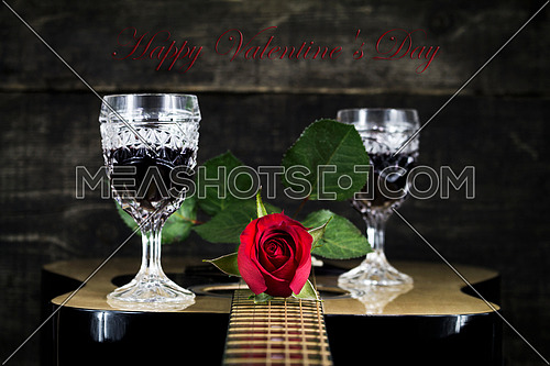 Red Rose and Wine Glasses Resting On Acoustic Guitar With Sign Happy Valentine's Day