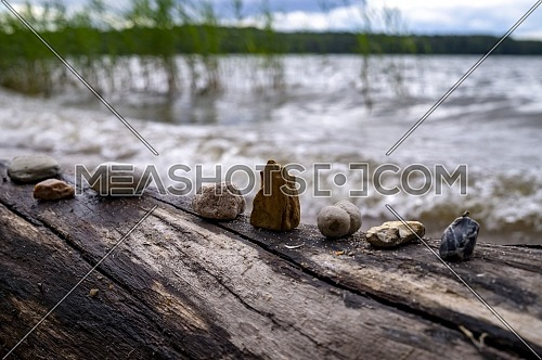 Row of stones and pebbles arranged on a log of driftwood on a beach at the edge of the sea in close up
