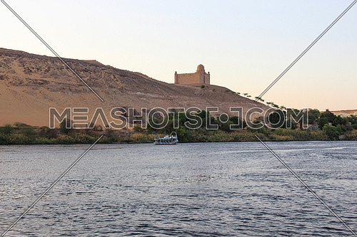 a photo from Aswan city , Egypt showing the Nile and some green area and aghakhan tomb at the top of the mountain