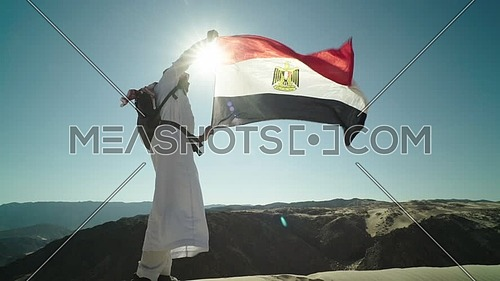 Follow shot for bedouin man holding Egyptian Flag in Sinai Trail from Ain Hodouda at day.