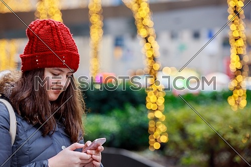 Beautiful stylish brunette young girl holding smart phone on a background with bokeh lights