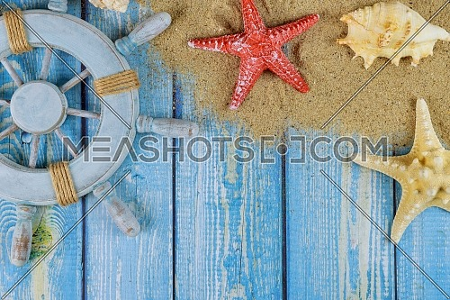 Sailor's captain's wheel with seashells, starfish, sand on blue wooden boards