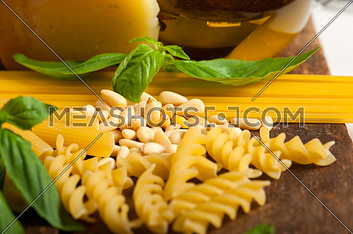 Italian basil pesto ingredients and raw pasta over old wood macro