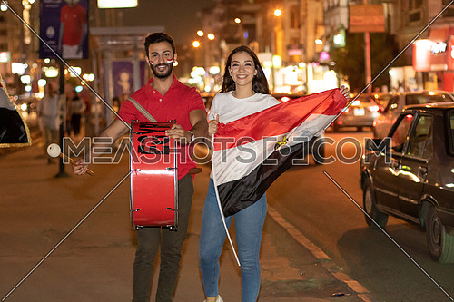 Egyptian football supporters in the street with Egyptian flag and a drum at night
