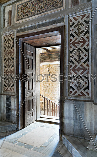 Wooden aged ornate opened door, decorated marble wall, and marble floor, Qalawun Complex, Moez Street, Medieval Cairo, Egypt