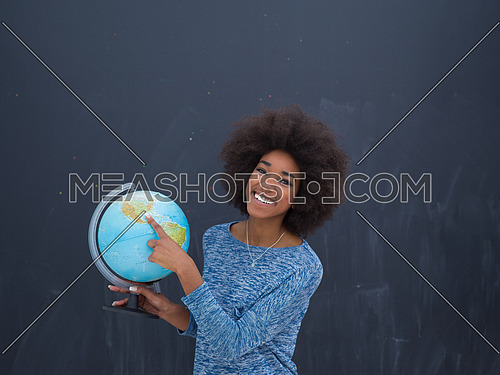portrait of a beautiful friendly African American woman with a curly afro hairstyle and lovely smile holding Globe of the world isolated on a gray background