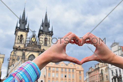 Close up young woman hands showing heart shape love symbol over cityscape with Cathedral of Our Lady before Tyn, Prague, Czech Republic
