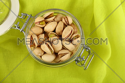 Close up fresh roasted pistachio nuts in glass jar over green yellow background, elevated, high angle top view, directly above