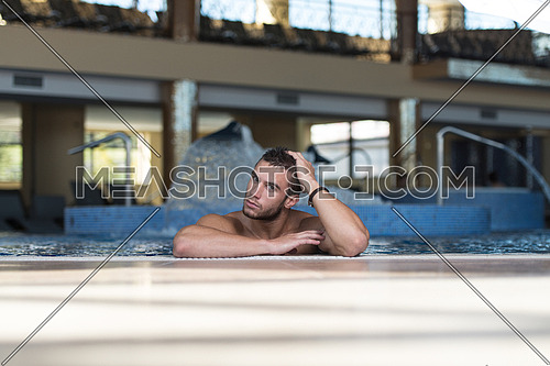 Happy Attractive Man Resting Relaxed On Edge Of Swimming Pool