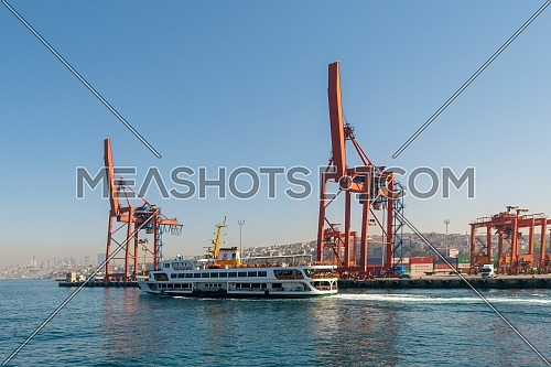 Day shot of the cranes in the shipyard of the Port of Haydarpasha, and passing ferry boat with city view in the background, Istanbul, Turkey