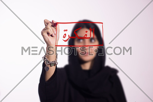 "Arabian middle eastern business woman writing with a marker on virtual screen in arabic الفكرة ""The Idea"" isolated on white background"