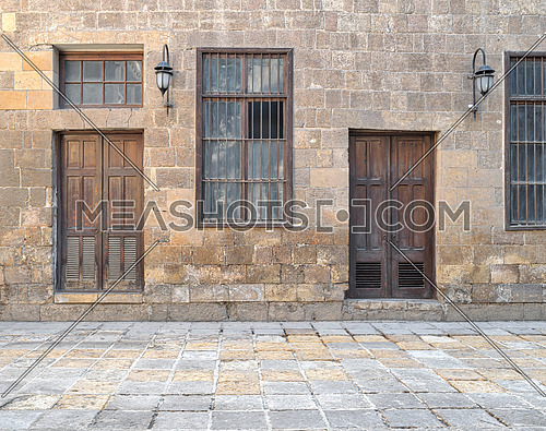 Facade of old abandoned stone bricks wall with wooden doors , windows covered with iron bars and lanterns, Cairo, Egypt