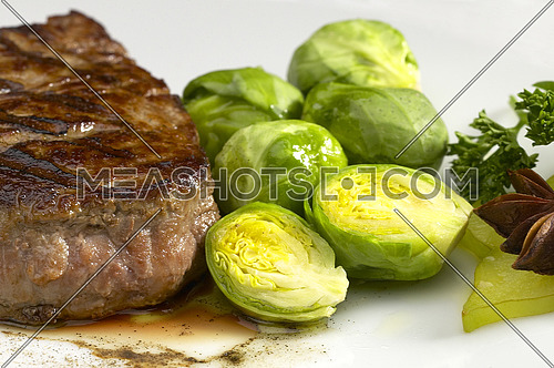 juicy filet mignon on plate with brussel sprout