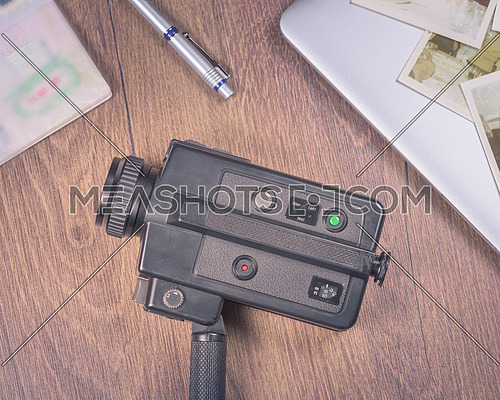 Vintage image with old black Video camera 8mm,old photo,laptop,pen and passport on wood table.
