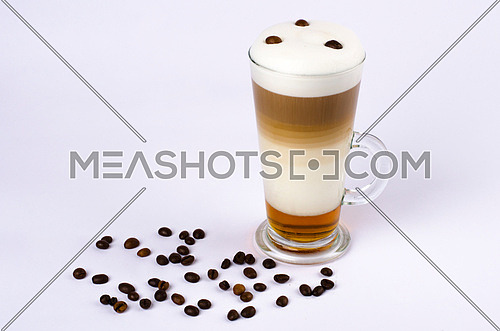 a coffee in glass with foam on top isolated on white with cofee beans on table