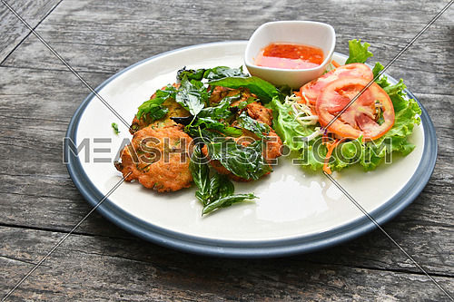 Close up plate of Thai fish and shrimp deep fried cakes croquettes snack with salad, basil leaves and hot chili sauce, high angle view