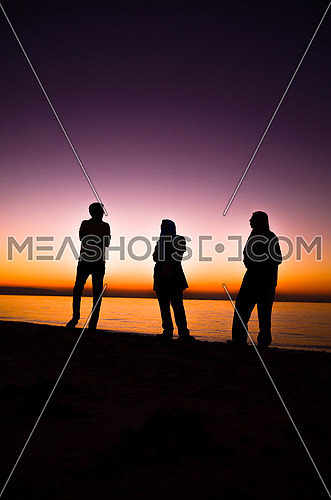 three friends enjoying their time at the beach during sunset