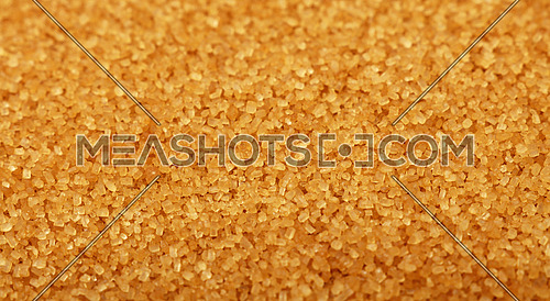 Close up background texture of brown raw cane sugar, high angle view, selective focus