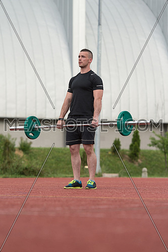 Young Man Doing A Dead Lift Exercise Outdoor
