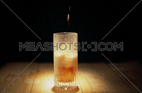 a fizzy drink filling glass on a table top isolated on black