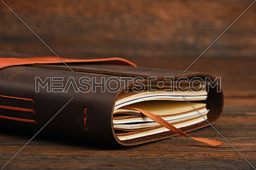 Handmade paper diary notebook in brown leather cover with orange bookmark over old vintage dark wooden table surface background