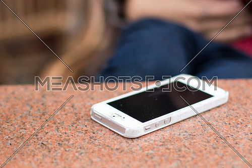 White mobile smart phone on a granite table