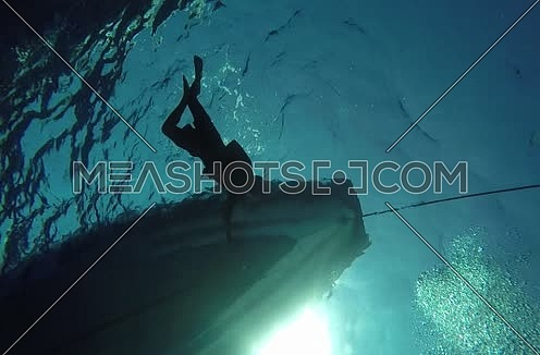 long shot underneath a Motor boats and swimmer at the Red Sea