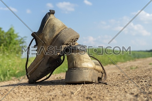 Pair of old worn leather hiking boots an a gravel path or road balanced on top of one another in a close up view