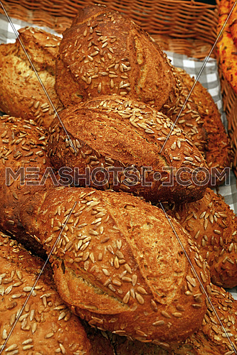 Close up selection of fresh bread loaves on retail display of bakery store, high angle view