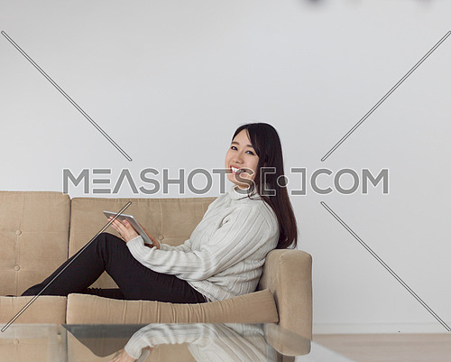 young happy asian woman sitting on sofa using Digital Tablet