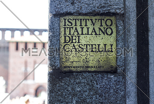 A copper sign on a wall in Milano