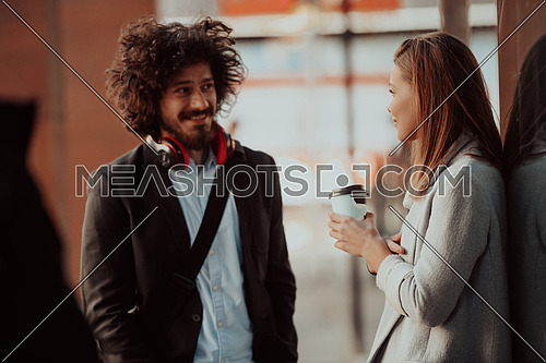 Two serious businessmen drinking coffee to take away. Man and a middle-aged woman in official shirt standing outside. Coffee break concept. High-quality photo