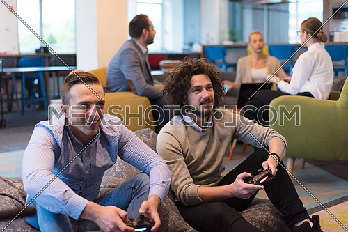 Work hard play hard. Workers Playing computer games in creative startup Office