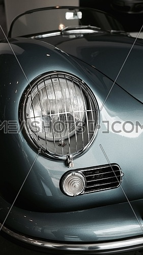 Headlight of a classic blue car parked