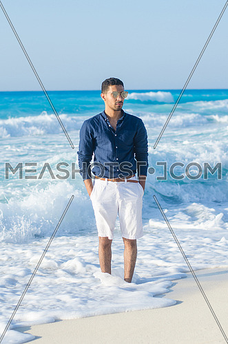 handsome man wearing a short and shirt by the sea