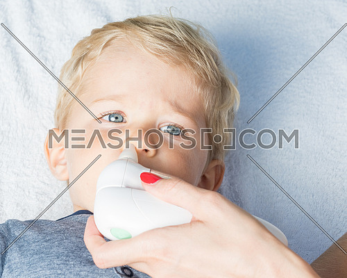 Mother using baby electric nasal aspirator. She is doing a mucus suction to twenty months baby boy.
